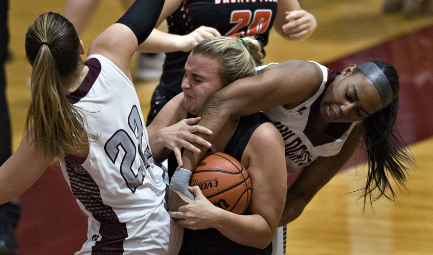 Warren County's Cor'shauna  Cunningham wrestles the ball from Brentsville's Ada Stanley during first quarter basketball action Friday night in Front Royal. Cunningham was charged with a foul on the play. Rich Cooley/Daily