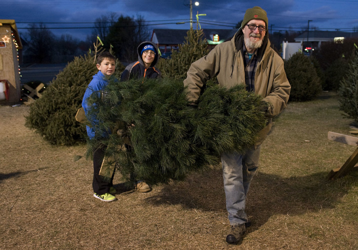 Front Royal Boy Scout Troop 52 Scoutmaster Jim Parsons, 76, leads  Scouts Jonathan Derflinger, 13, left, and Alex Kubela, 14, right,  as they  carry a white pine Christmas tree outside their stand at Royal Plaza Shopping Center on South Street in Front Royal on Friday. Parsons is retiring after being a scoutmaster since 1985.  Rich Cooley/Daily