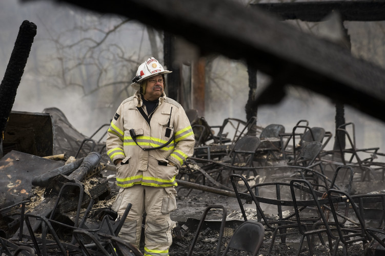 Warren County Fire and Rescue Chief Richard A. Mabie walks inside the burned-out pool house at North Fork Campground on Tuesday morning. Rich Cooley/Daily