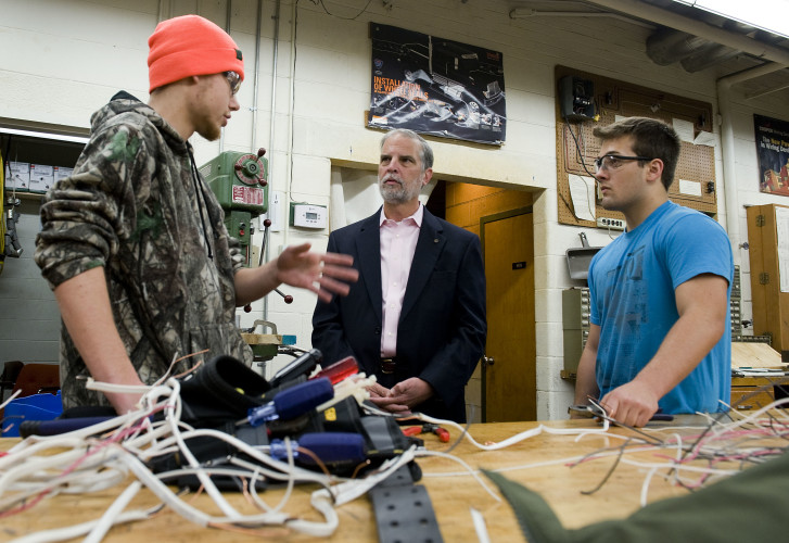 State Sen. Mark D. Obenshain, center, chats with second year Triplett Tech electricity students Shane Piercy, 18, left, and Jacob Richards, 18, during a tour of the technical school on Wednesday. Obenshain and a host of local and elected leaders had breakfast and toured the facility.  Rich Cooley/Daily