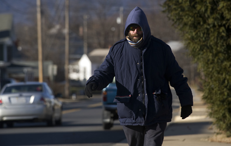 Jim Mundell takes an afternoon walk along East Queen Street on his lunch break from the Strasburg Post Office on Thursday afternoon. Mundell battled cold temperatures and wind to get his power walk in.  Rich Cooley/Daily