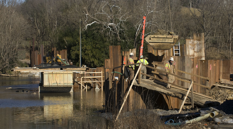 A crane operator lifts this crane pan out from inside this coffer dam at the Morgan Ford bridge construction site in Warren County on Monday. A small excavator is digging inside the dam for this bridge pier along the south side of the bridge.  Rich Cooley/Daily