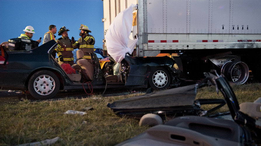 Fire and rescue personnel stand outside this car that ran underneath a tractor trailer that was parked on the shoulder of Interstate 81 southbound near the Woodstock exit Wednesday evening. Rich Cooley/Daily