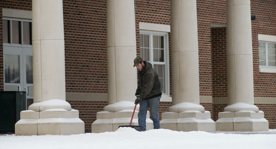 Brady Johnson, a custodian/maintenance employee of Warren County Public Schools, moves snow outside the entrance of Skyline High School in Front Royal on Friday.  Rich Cooley/Daily