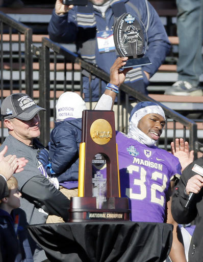 James Madison head coach Mike Houston, left, watches as running back Khalid Abdullah (32) holds up the most valuable player award after their 28-14 win over Youngstown State in the FCS championship NCAA college football game, Saturday in Frisco, Texas.  AP