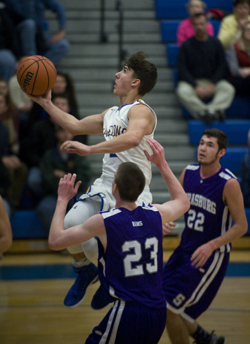 Central's Mason Marston drives down the lane for a layup as Strasburg's Samuel Hopkins, left, and Matthew Hoover, right, look on during first quarter action Thursday night in Woodstock. Rich Cooley/Daily