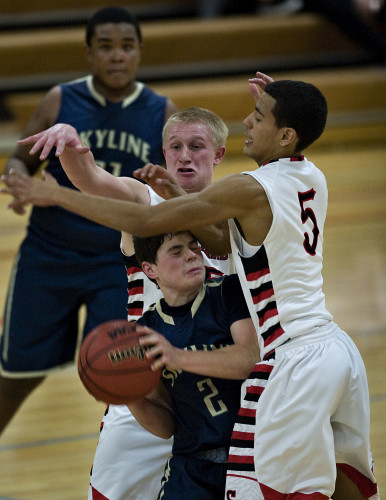 Skyline's Ty Clingerman gets caught in a double team by Sherando's Alex Morefield, left, and Aaron Banks, right, during second quarter boys basketball action Monday night in Stephens City.  Rich Cooley/Daily