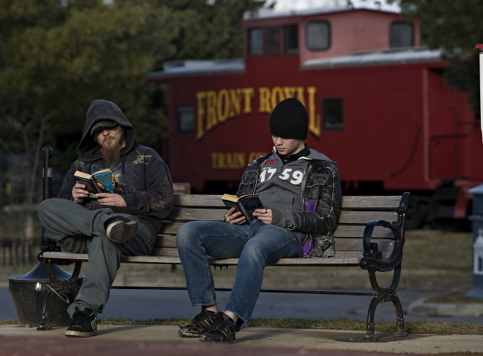 Eric Krieger, left, and Matt Ciskanik, right, read outside the gazebo area on East Main Street in Front Royal on a mild winter afternoon. Rain is expected today but Saturday is looking good for outdoor activity with a high of 60. Rich Cooley/Daily