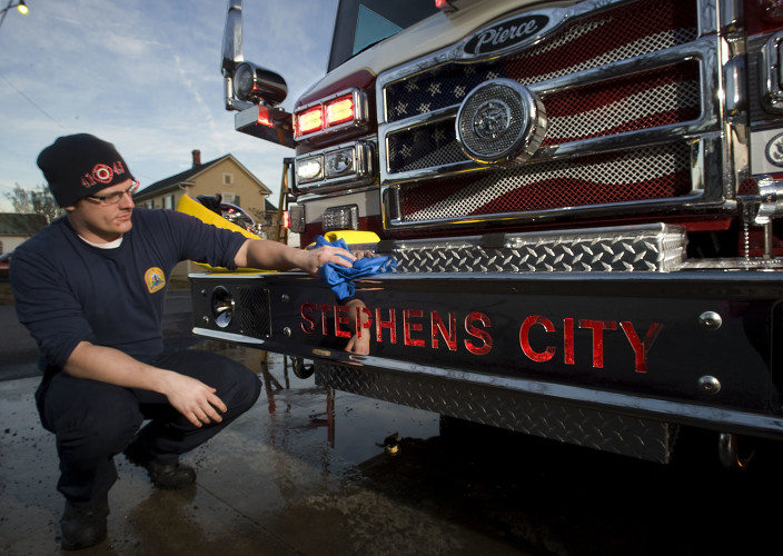Brian Meade, a Frederick County career firefighter/EMT, wipes down the front bumper of Stephens City's new Pierce pumper outside the fire station Thursday evening. The fire apparatus has a laser etched backlight that is the first for Pierce to manufacture.  Rich Cooley/Daily
