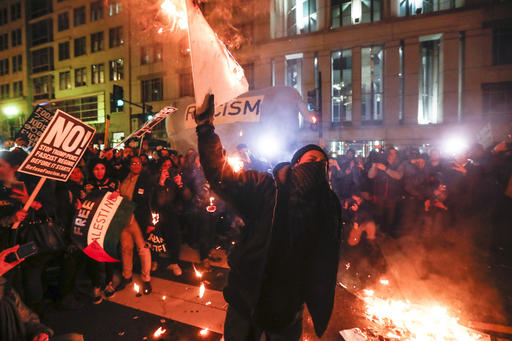 Protesters burn signs outside the National Press Building ahead of the presidential inauguration on Thursday evening in Washington.  AP Photo/John Minchillo