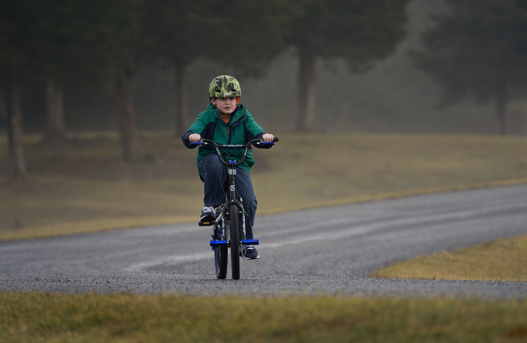Jack Ham, 10, of Toms Brook, rides his bike through light fog along this   stretch of road in Shenandoah County's Park in Maurertown recently.  Rich Cooley/Daily