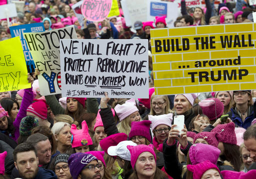 Women with bright pink hats and signs begin to gather early and are set to make their voices heard on the first full day of Donald Trump's presidency on Saturday in Washington.  Organizers of the Women's March on Washington expect more than 200,000 people to attend the gathering.  Other protests are expected in other U.S. cities.  AP Photo/Jose Luis Magana