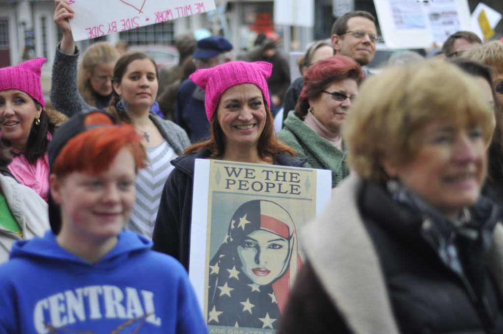 "A woman wears a pink pussyhat and holds a poster during the women's march held in Woodstock on Saturday. The knitted hat was visible in women's marches in  Washington, D.C. , around the nation and the world on Saturday. The Associated Press reported Saturday that over a million people came out to ""send President Donald Trump an emphatic message on his first full day in office that they won't let his agenda go unchallenged."" Jake Zuckerman/Daily"