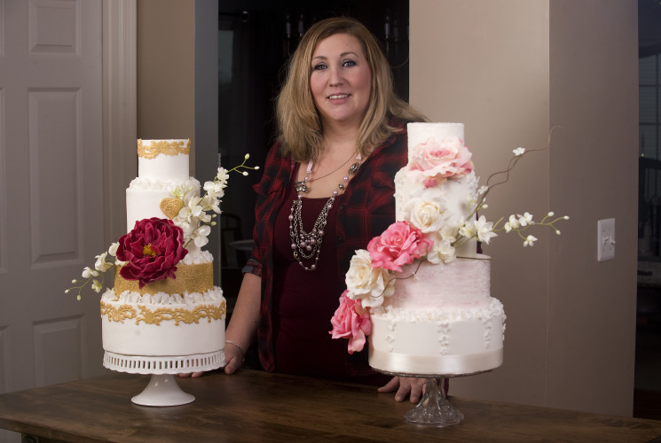 Jennifer Frey, owner/cake designer for Tiers in Heaven, stands beside a display  of her four-tier cakes with faux flowers. The cake at right has a double barrel tier that  features two cakes on one tier. Rich Cooley/Daily