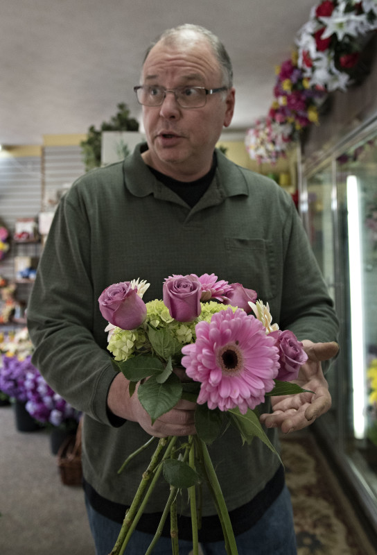 Chuck Hepner, owner of the Valley Flower Shop and Greenhouse in Woodstock, holds a handful of typical flowers that a bride might use in her bouquet. Rich CooleyDaily