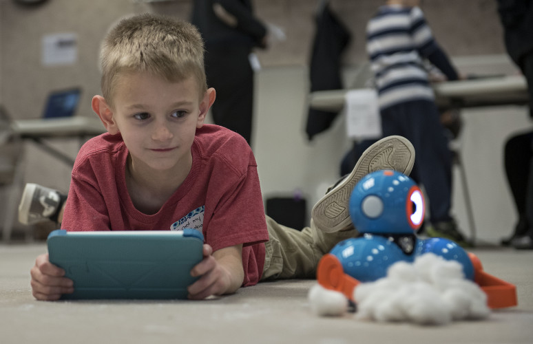 Lincoln Bennett, 7, of Edinburg, a second grader at W.W. Robinson Elementary, uses an iPad to control this robot that pushed cotton balls along the carpet during the Robotics and Coding Open House on Thursday at the Shenandoah County Administration Building in Woodstock.  Rich Cooley/Daily