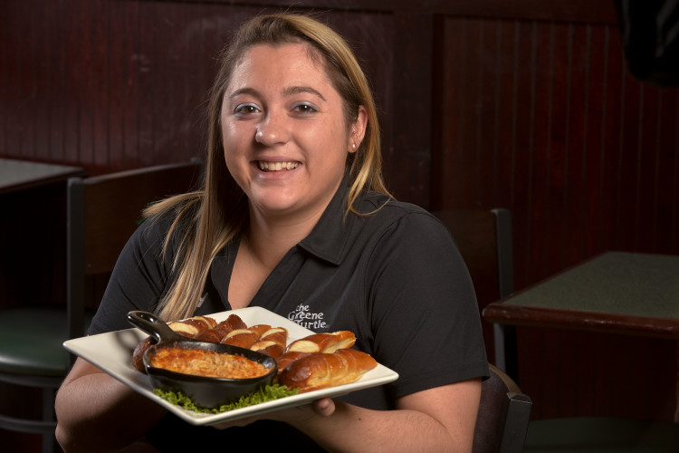 Allison Palmer, 22, of Strasburg, a server at the Greene Turtle in Winchester, holds a plate of crab dip served with Bavarian pretzel sticks. The popular appetizer is part of the Super Bowl menu for Sunday. Rich Cooley/Daily