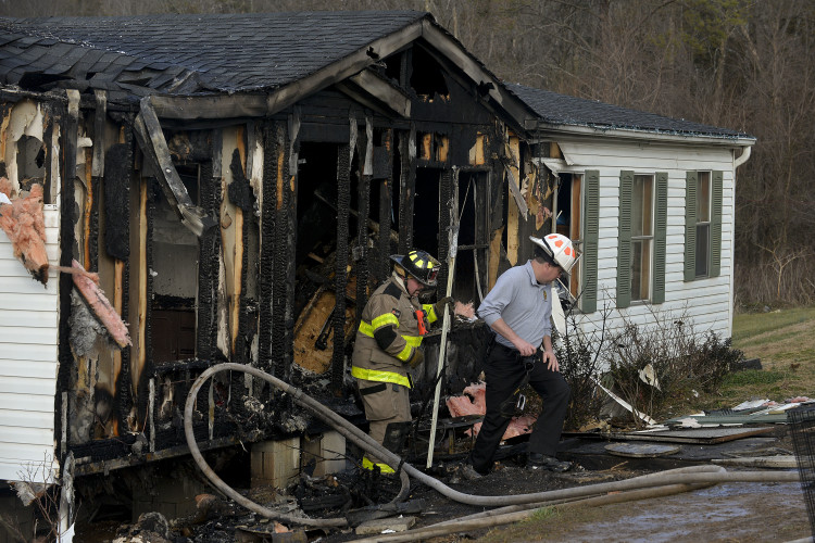 Edinburg firefighter Nathan Helsley, left, and Shenandoah County Fire Marshal David Ferguson walk outside this home on Jerome Road in Conicville that was destroyed by fire Tuesday afternoon. Rich Cooley/Daily