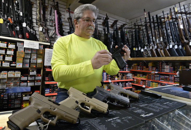 Eugene Del Gallo, assembles a glock pistol inside G & S Guns and Wildlife Shop in Woodstock. Del Gallo, who co-owns the shop with his wife, has noticed a spike in hand gun sales. Rich Cooley/Daily