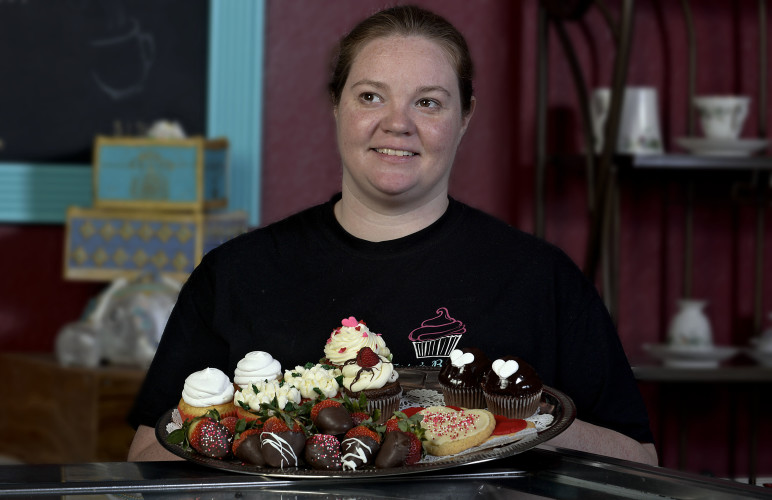 Tiffany Akers-Hockman, owner of Tippy's Bakery in Strasburg, holds a plate of Valentine treats,  including  sugar cookies, chocolate-covered strawberries and assorted cupcakes. Rich Cooley/Daily