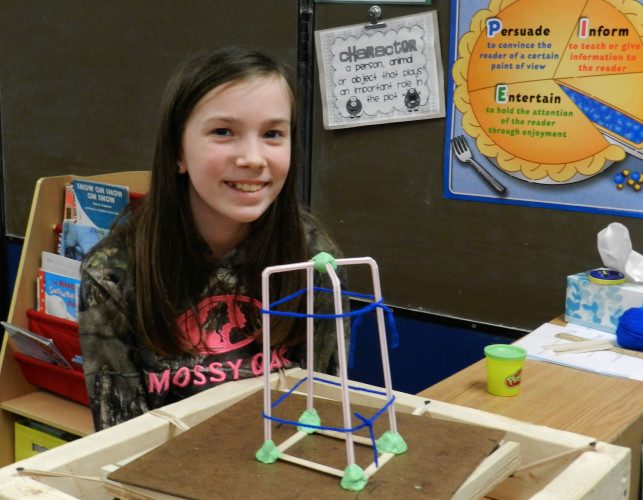 Sophia Sebeck, 10, of Maurertown, created a house of putty, popsicle sticks, straws and yarn to withstand a simulated earthquake for STEM Night. Photo by Kaley Toy/Daily