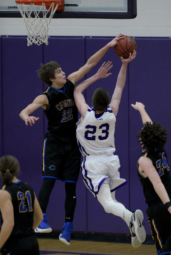 Central's Luke Estep gets a hand on the ball as Strasburg's Sameul Hopkins  goes up for a shot during second quarter basketball action Friday night in Strasburg. Rich Cooley/Daily