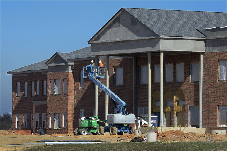 Construction workers use  a lift outside the front entrance of the Warren County Middle School under construction off Leach Run Parkway and Happy Creek Road in Front Royal. Rich Cooley/Daily