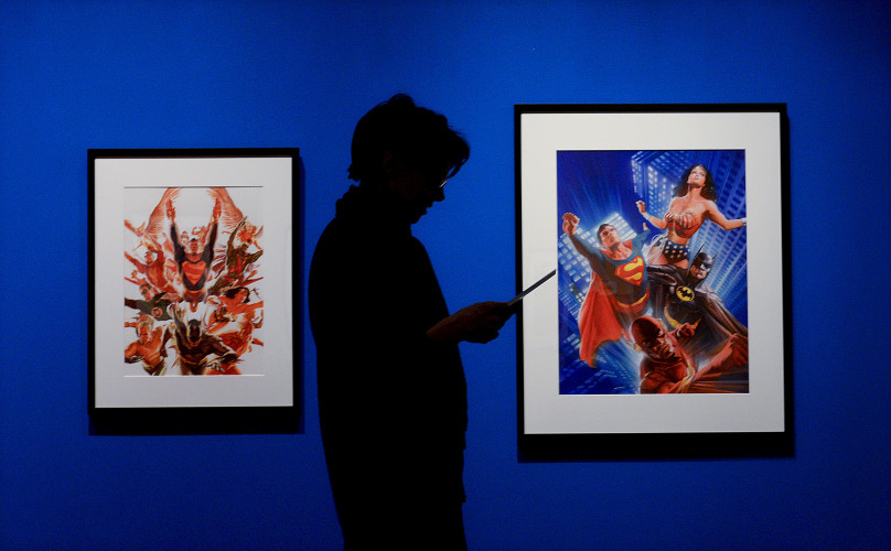 "Nancy Huth, deputy director of arts and education at the Museum of Shenandoah Valley, reads over documentation of the opening of the exhibition ""Superheroes and Superstars: The Works of Alex Ross."" The display includes the ""Worlds Greatest Superheros 2005,"" left, and ""Superpeople 2016,"" right.  Rich Cooley/Daily"