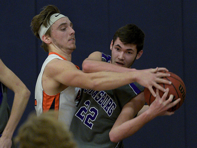 Clarke County's Brett McDonald wraps up Strasburg's Matthew Hoover during second quarter basketball action Thursday night in Berryville. McDonald was charged with a foul on the play.  Rich Cooley/Daily