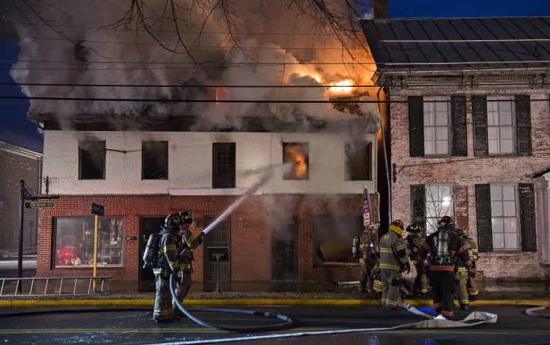 Fire shoots out of the roof of this building at Main and East Locust streets in Woodstock early Friday morning. Rich Cooley/Daily
