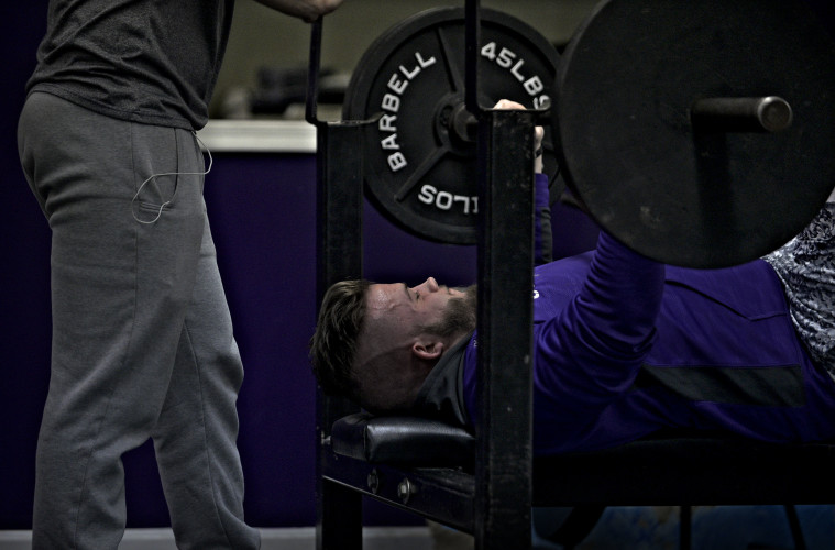 Caleb Warren performs a bench press at Tight'n Up Gym in Strasburg recently. Warren, along with a group of fellow Strasburg High School students, has helped organize a weightlifting competition to raise funds for the nonprofit gym.  Rich Cooley/Daily