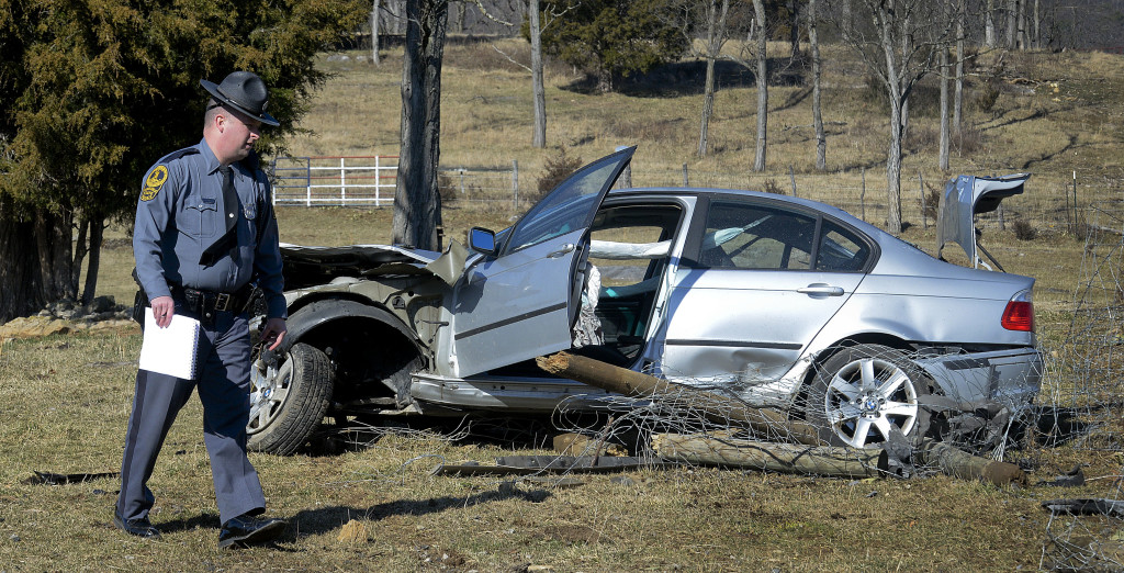 Virginia state trooper C.S. Cline walks around this car that crashed off Mt. Olive Road near Toms Brook following a police pursuit on Interstate 81 on Monday. The car took out a large section of fencing and ended up in a field. Rich Cooley/Daily