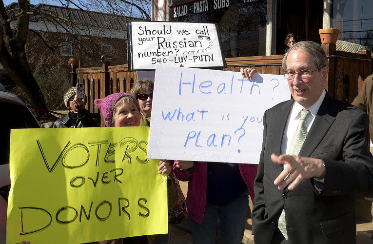 U.S. Rep. Bob Goodlatte addresses protesters outside Carmella's Restaurant in Edinburg on Monday following a private luncheon among area leaders.  Rich Cooley/Daily