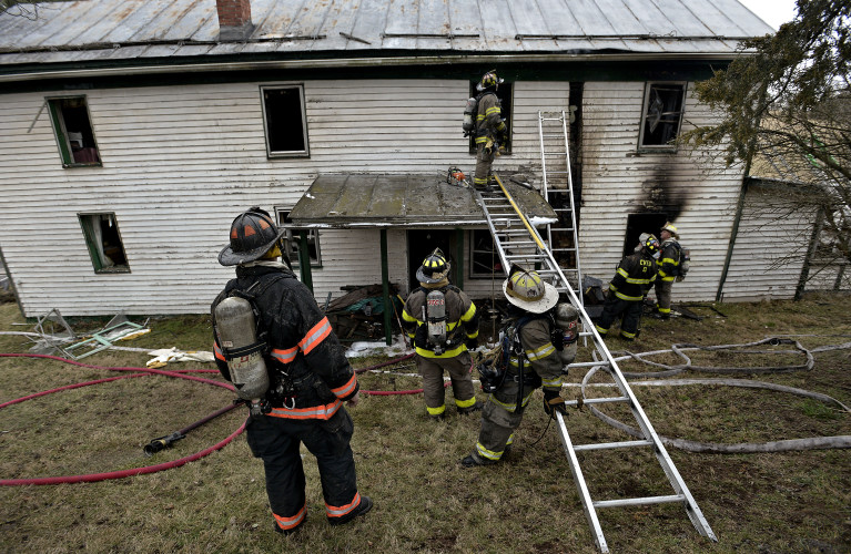 Firefighters stand outside the rear of home at 1328 Pepper Road where one person died on Tuesday morning. The victim's identity has not been released. Rich Cooley/Daily