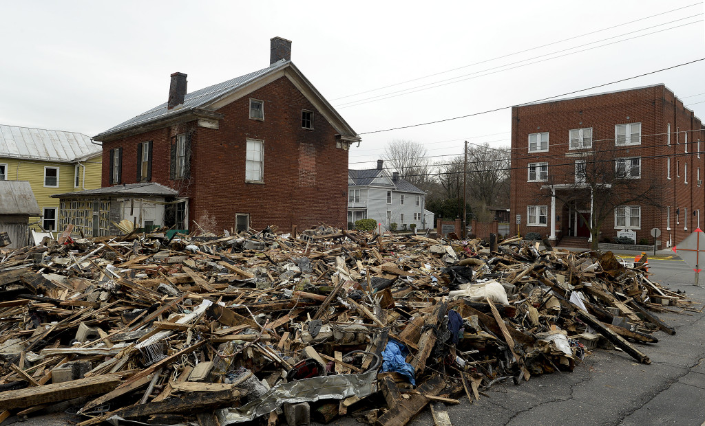 Debris from the razing of the retail-residential building at 164 N. Main St in Woodstock remains piled up, blocking East Locust Street. The building caught fire last Friday. The rubble will eventually be transported to the landfill.   Rich Cooley/Daily