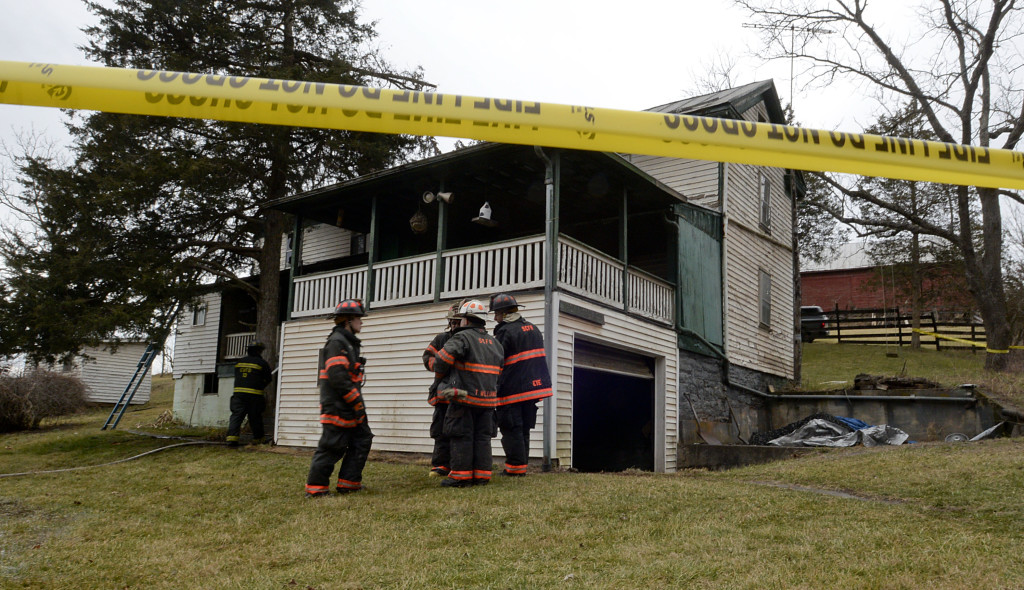 Shenandoah County firefighters stand outside the residence at 1328 Pepper Road in Mount  Jackson on Tuesday morning.  Rich Cooley/Daily