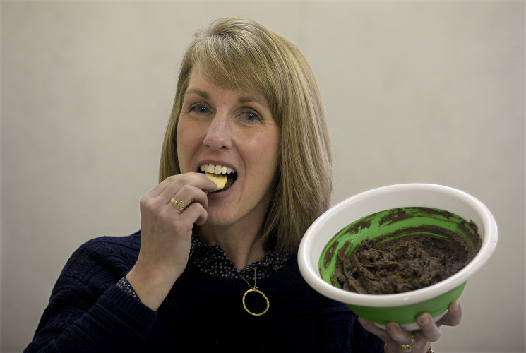 Maureen Bierling Watts, a registered dietician, holds a bowl of brownie batter dip that she featured during a food demonstration Thursday at the Loaves and Fishes Food Pantry in Front Royal. Watts used black beans instead of cooking oil to add protein for a healthier treat.  Rich Cooley/Daily