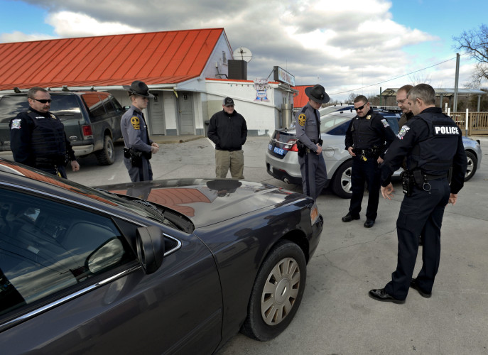 Area police officers look over the Crown Victoria police cruiser that a wanted suspected backed into outside the New Star Market located on John Marshall Highway in Strasburg on Thursday. Strasburg police Capt.  Wayne Sager tried to apprehend the suspect before he led officers in a pursuit into West Virginia.   Rich Cooley/Daily