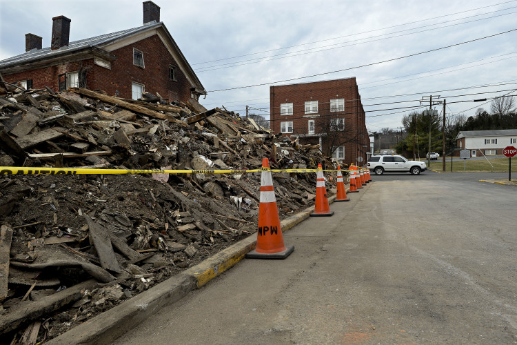 Debris from this building that burned at 210 Main St.  in Woodstock has been moved off East Locust Street and piled back up on the former site.   Rich Cooley/Daily