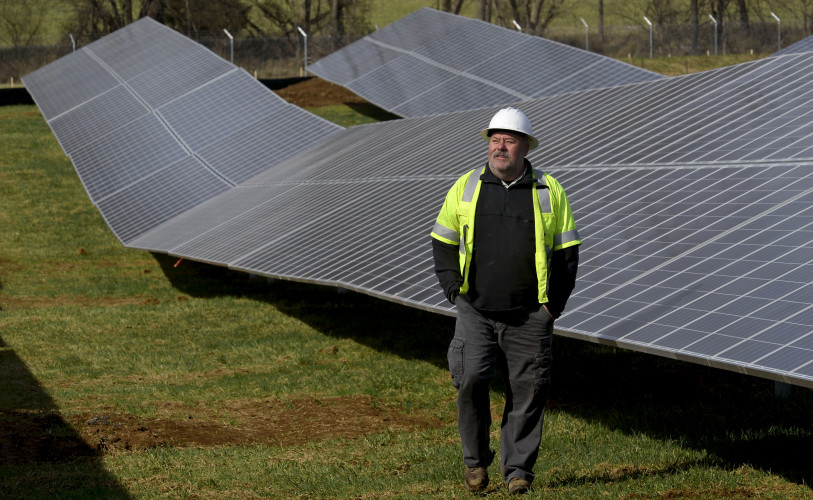 David Jenkins, interim director of Energy Services for the Town of Front Royal, walks along this line of solar panels on this 15-acre tract off Manassas Avenue in Front Royal on Wednesday.  Rich Cooley/Daily