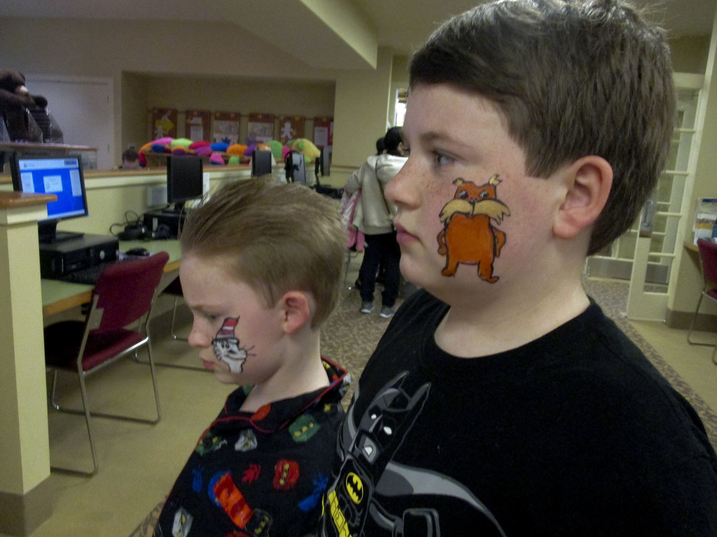 Elijah Pennington, 10, and Israel Pennington, age 7, sons of Crystal Pence, of New Market, show off their painted faces during the New Market Area Library's celebration of Dr. Seuss' birthday on Feb. 13 . Students from Stonewall Jackson High School and Shenandoah Valley Academy, along with adult volunteers, helped children celebrate with a birthday cake, cooking green eggs and ham, listening to Dr. Seuss books, face painting and making Dr. Seuss hats. Children also took home Dr. Seuss bookmarks and stickers. Liz Gum, of New Market, created and donated a  birthday cake. Photo courtesy of  Karen Whetsel