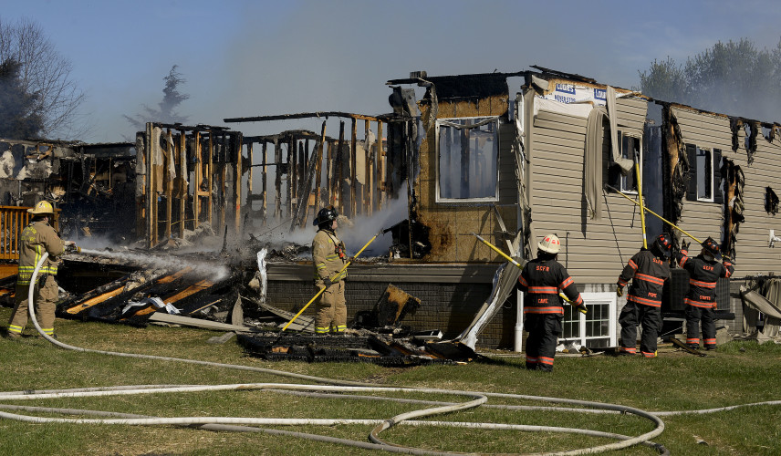 Firefighters work to extinguish hot spots on this Edinburg fire Wednesday afternoon.  Rich Cooley/Daily