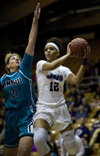 James Madison University's Precious Hall drives to the basket as University of North Carolina Wilmington's Jenny DeGraaf defends during first half basketball action at the Colonial Athletic Association's quarter finals held Thursday evening at James Madison University. Rich Cooley/Daily