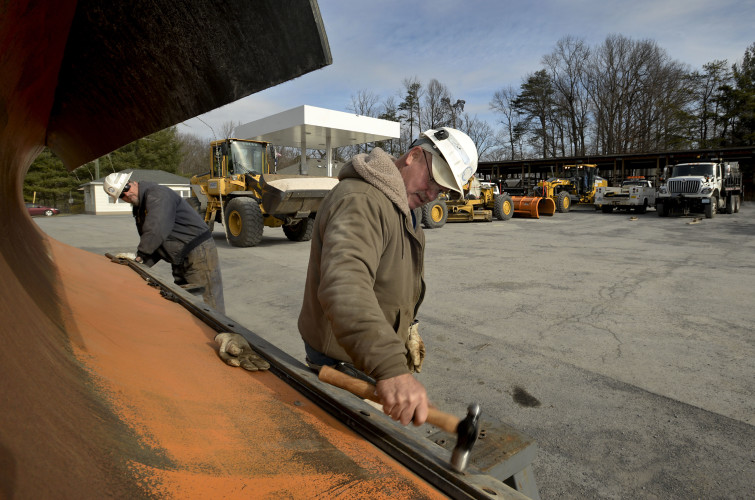 Todd Heier, left, and Rick Roberts, right, both maintenance operators for the Virginia Department of Transportation, install a new blade on a snow plow outside VDOT'S Toms Brook district office Monday morning. Area crews were busy Monday preparing for the  winter storm.  Rich Cooley/Daily