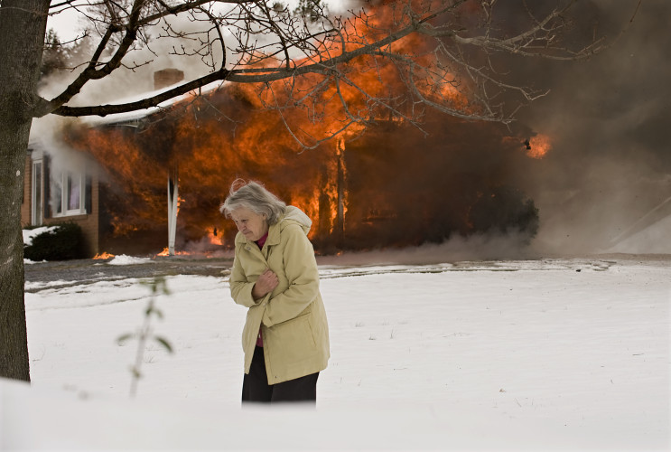 Gloria Ingram walks across her front yard beside her neighbor's home, which caught fire on Wednesday.   Rich Cooley/Daily