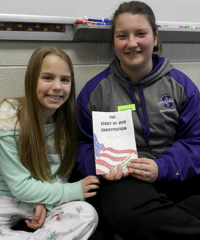 At left, Madelynne Martin, 9, of Strasburg, is presented a Constitution book by Katie Smoot, 17, of Strasburg, on Thursday morning. Kaley Toy/Daily
