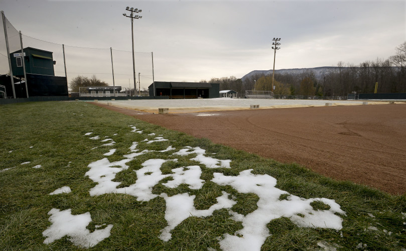 Snow clings to the baseball field at 1st Bank Park in Strasburg on Friday evening. Area athletic directors are struggling to reschedule spring sports events after snow and cold temperatures this week brought events to a standstill . Rich Cooley/Daily