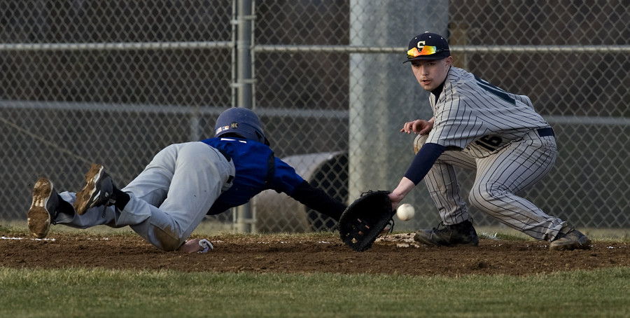 Central's Josue Rosario dives back to first on a pick off attempt as Skyline's first baseman Colin Rankin tries to make a play during third inning action Monday night in Woodstock. Rosario was safe on the play. Rich Cooley/Daily