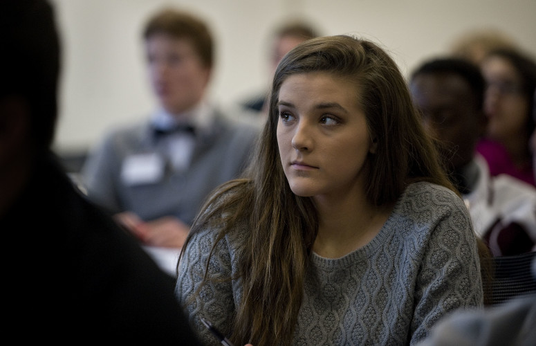 Jessica Sims, 18, a senior at Skyline High School, listens to Elizabeth Cottrell, chairman of the board, speak during Bank Day at First Bank's Operation Center in Strasburg on Tuesday. Rich Cooley/Daily