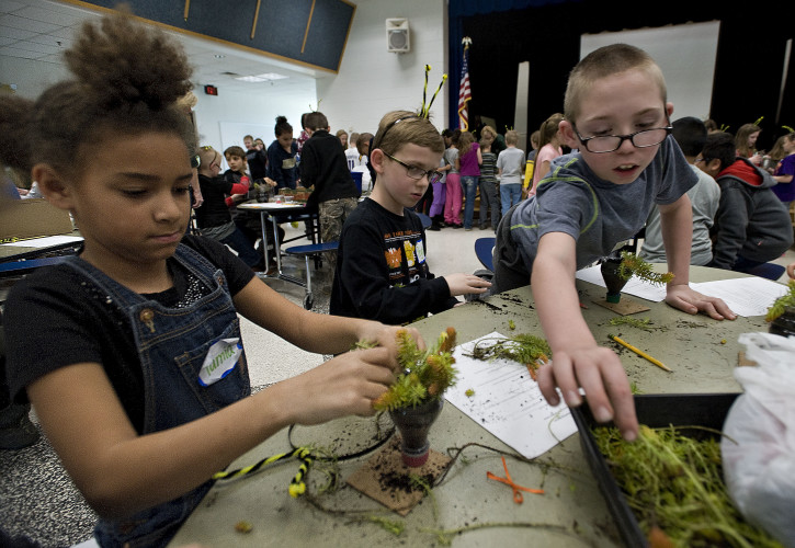 Tamia Center, 8, left, Peyton Vogeler, 9, center, and Logan Vedarn, 9, right,  assemble their sedum plants inside the cafeteria at Hilda J. Barbour Elementary School. Shenandoah Valley Master Gardeners sponsored a Circle of Life program there last week that focused on how plants come to life and make more plants. Rich Cooley/Daily